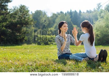 Sweet bonding. Charming young mother sitting on the grass, holding her little daughter in her lap and playing pat-a-cake with her while smiling broadly