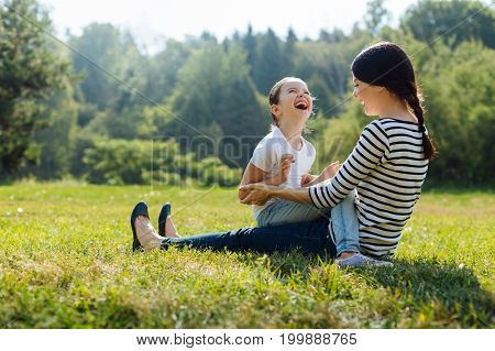 Infections laughter. Pleasant young mother sitting on the grass, holding her little daughter on her lap and laughing together with her while discussing something funny