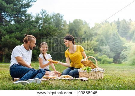 Relaxing weekend. Beautiful young mother giving her daughter a banana while the entire family enjoying picnic in the park, sitting on the grass