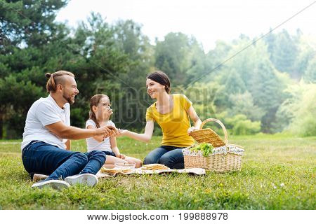 Delicious meal. Cheerful pleasant young family sitting on the grass in the park and sharing food while having a picnic