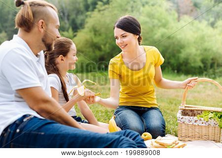 Bon appetite. Pleasant caring young mother giving a peeled banana to her little daughter while having a picnic with a family in the park