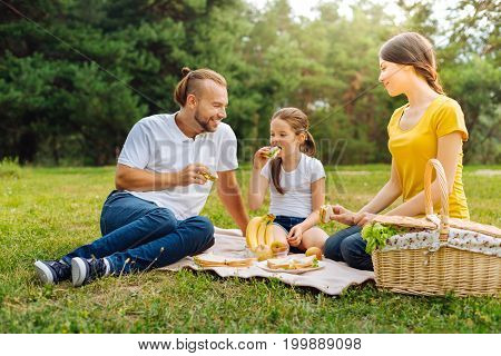 Delicious snacks. Pleasant cheerful young family sitting on the grass in the meadow and tucking into sandwiches