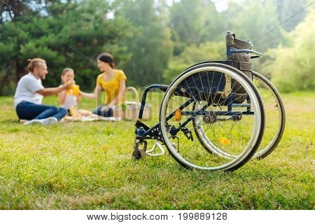 Toast to health. The focus being on a wheelchair of a pleasant young man clinking glasses with juice with his family while being on a picnic in the forest