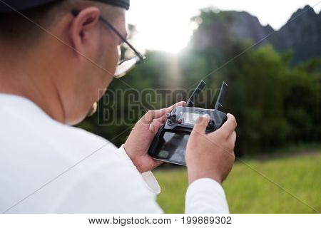 a man using drone remote controller, in sunrise