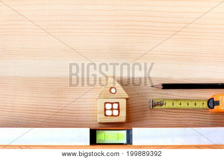 Installation with house level tape measure and pencil on wooden surface / most important tools for construction