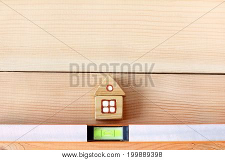 small wooden model of the house and a building device on wooden boards from above/ Necessary building level okay