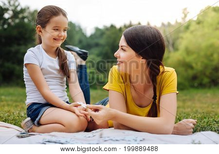 Thank you. Merry little girl taking a missing piece of a puzzle from her mothers hands while they doing a puzzle on a picnic in the park