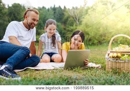 Interesting film. Pleasant young family sitting on the grass and watching a film on the laptop while having a picnic in the park