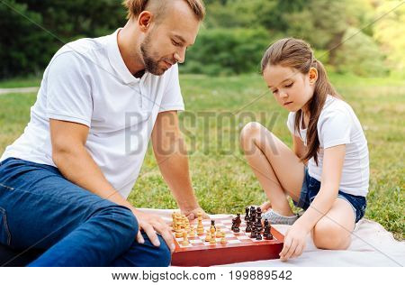 Little prodigy. Pleasant smart girl playing chess with her beloved father while having a picnic in the park