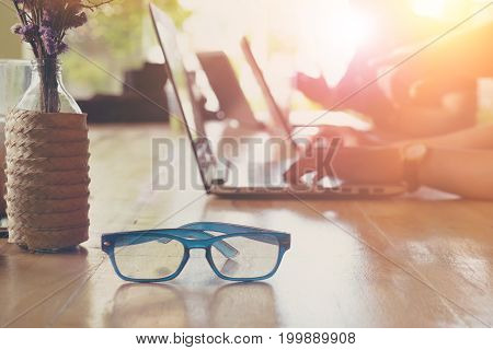 Eyeglasses on the foreground unrecognized businessmen interactive with laptop on the background
