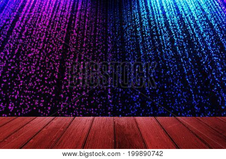 empty wooden floor or wooden terrace with blurred view of curtain of falling water with colorful led light on dark background copy space for display of product or object presentation vintage tone