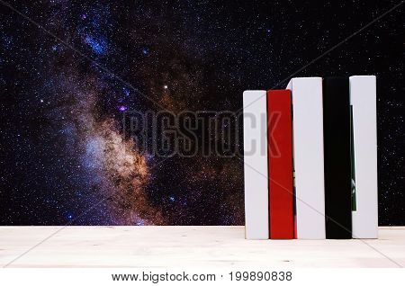 stack hardback book on wooden shelf or desk no labels blank spine with milky way galaxy background soft focus color tone effect education back to school outer space science concept