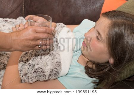 cute girl child taking pill with glass of water