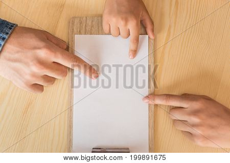 Cropped Shot Of Young Family Pointing At Blank Paper On Clipboard