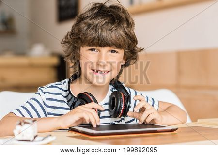 cute little boy with digital tablet and headphones in cafe