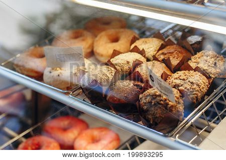 Coffee shop window with baked food pastries. Closeup macro group of fresh vegan organic muffins and donuts in basket.