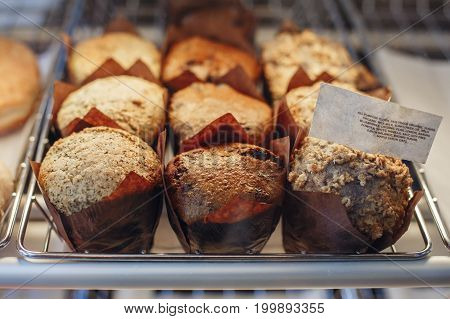 Coffee shop window with baked food pastries. Closeup macro group of fresh vegan organic muffins in basket.