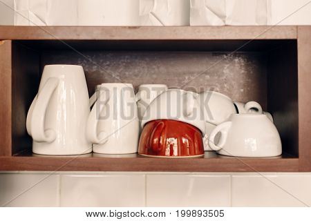 White coffee cups stacked on shelf in coffee shop. Interior of cafe with tea mugs. Toned with filters. Retro vintage style.