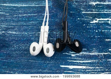 Small White And Black Headphones Lie On A Blue Denim Background. Horizontal Frame