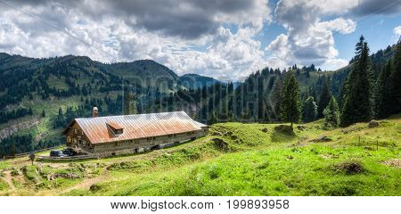 Old alpine hut with meadow in the Alps. Bavaria, Allgau, Germany. Traditional farming in the bavarian mountains.