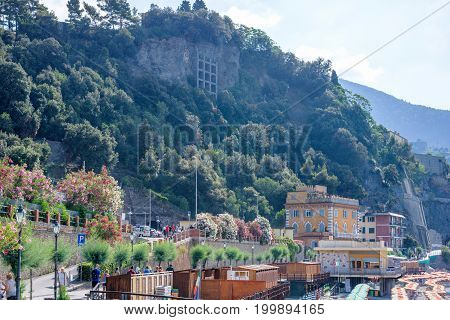 Beautiful daylight view to beachline and green mountains in fog. Monterosso al Mare, Italy. Cinque Terre