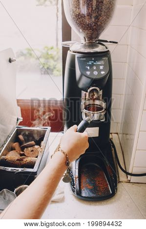Closeup of Caucasian barista hand with filter holder grinding fresh roasted coffee beans. Preparing coffee in coffee shop cafe.