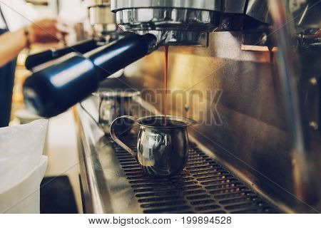 Closeup of coffee espresso machine making coffee. Thin coffee stream flow coming pouring to metal mug jug. Toned with warm yellow film filters.