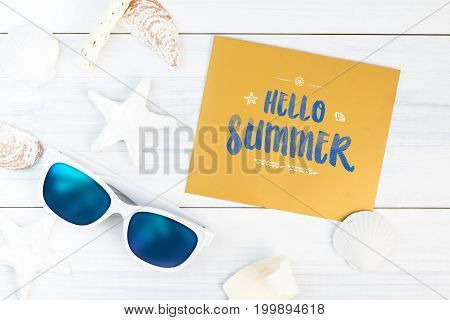 Hello Summer word on gold paper card white Summer Beach accessories (White sunglassesstarfishstraw hatshell) on white plaster plank wood table top viewSummer vacation quote.