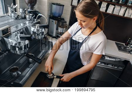 Young Caucasian woman barista using tamper to press ground coffee into portafilter to make espresso hot drink. Small local business work in cafe.