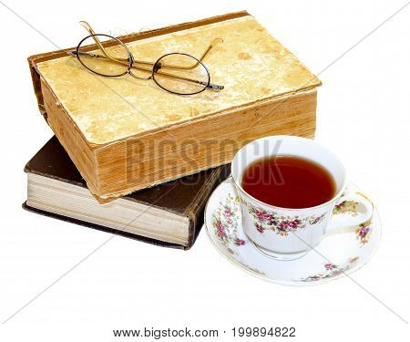 On An Old Book With A Torn Binding. Broken Spine Are Glasses And A Cup Of Tea