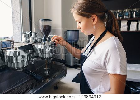 Portrait of Caucasian barista woman with filter holder making fresh espresso cappuccino. Server pouring hot drink from professional machine to metal jug. Preparing coffee in restaurant shop cafe.