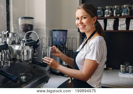 Portrait of happy beautiful young Caucasian smiling woman barista holding milk jug for making coffee using coffee machine. Small local business with organic hot drinks products. Toned with filters.