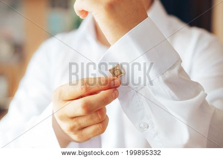 The man buttoned the cuff links on his sleeve. Close-up. Businessman or groom. Man's style