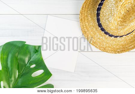 Blank white paper card on wood table top view with straw hat and blur foreground tropical palm leaf Summer vacation conceptMock up template for adding your design or text.