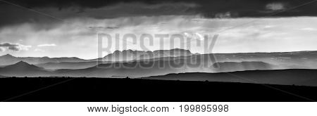 Monochromatic sunlight sunset with layered mountains and moody sky. Amazing panoramic view of the landscape in Iceland.