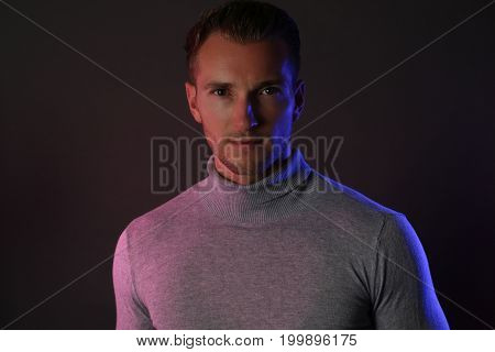 handsome man wearing a gray turtleneck on gray background