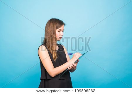 Business woman writing on a clipboard, isolated on a blue background.