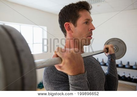Close up of male confident athelte lifting barbell at gym