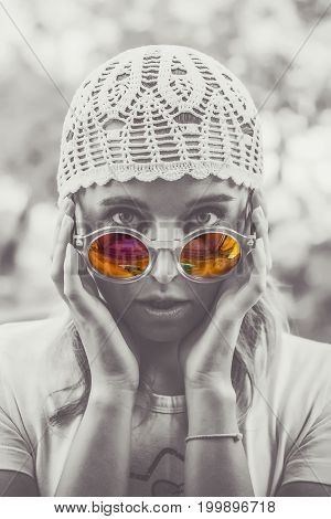Portrait of a beautiful girl in trendy sunglasses with colorful reflection. Toned black and white.