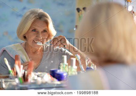 Portrait of happy senior woman brushing her teeth