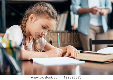 cute focused little girl writing in notebook and doing homework