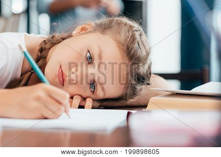 sad little girl writing in notebook and doing homework