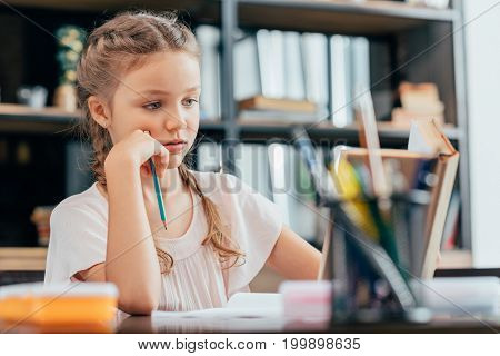 focused cute little girl holding pencil and doing homework