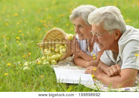 Senior couple lying on green grass, woman holding apple, man in eyeglasses reading book