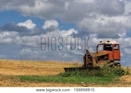 BULLDOZER - Wreck of a machine standing on a field