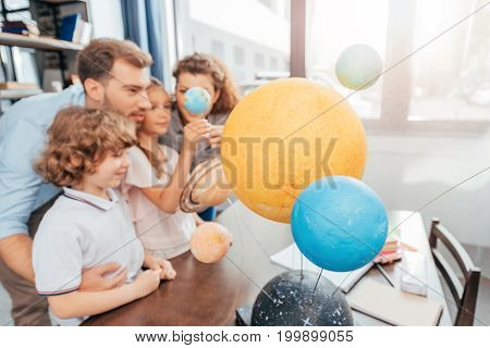 Young Happy Family Making Solar System Model For School Project