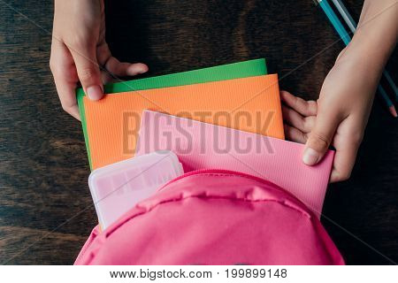 Cropped Shot Of Girl Pulling School Supplies From Backpack