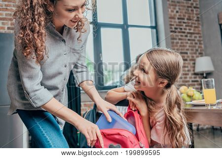 Beautiful Young Mother Giving School Lunch To Daughter