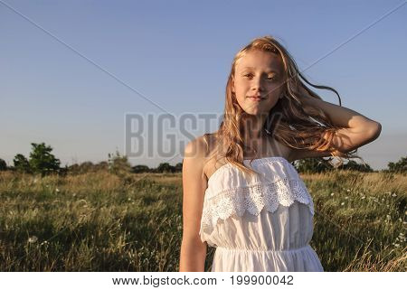 Young girl with blond developing hair standing in a field