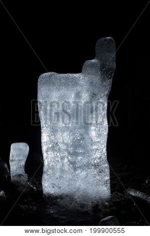 Ice stalagmite in a cold cave. Winter icicles iluminated with battery and candles
